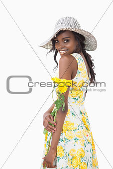 Woman standing holding yellow flowers