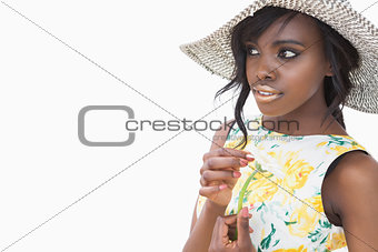 Woman wearing summer hat and holding daisy