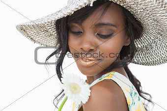 Woman wearing summer hat and holding white flower