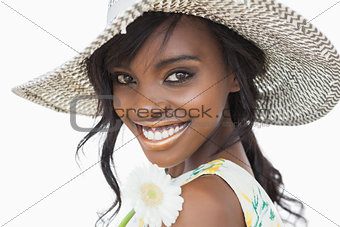 Woman smiling and holding white flower in a sun hat