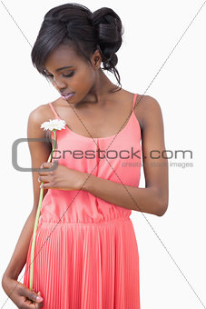 Woman standing holding a flower
