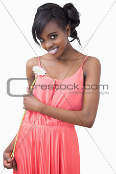Woman standing holding a flower smiling