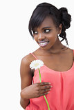 Girl standing holding a flower while smiling against white background
