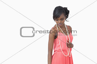 Woman looking down wearing pearls and pink dress