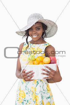 Woman with sun hat holding box with fruits