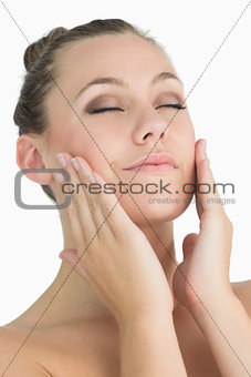 Blonde woman touching her face