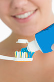 Smiling woman putting toothpaste on toothbrush