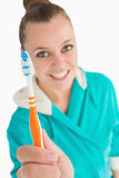 Woman with bathrobe showing her toothbrush