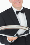 Waiter smiling and holding a silver tray
