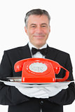 Smiling waiter holding a red phone