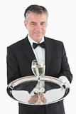 Smiling waiter serving glass of wine on tray