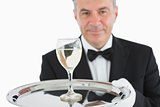 Smiling man serving glass of wine on platter