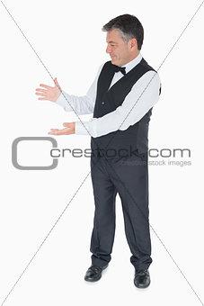 Man in suit showing us something