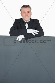 Man in suit leaning on grey board