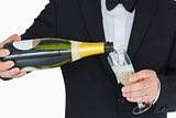Well-dressed man pouring champagne