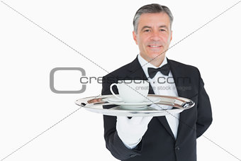 Smiling waiter holding tray with coffee cup