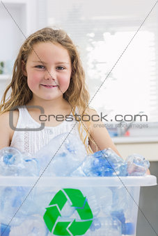 Little girl carrying box full of empty plastic bottles