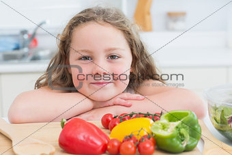 Girl leaning beside vegetables