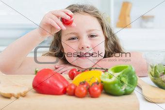 Little girl holding up cherry tomato