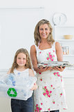 Mother and daughter standing in the kitchen with waste for recycling