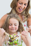 Close up of mother and daughter during mixing salad