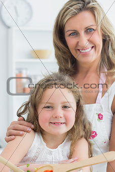 Mother hugging daughter and making salad