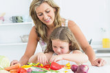 Mother teaching her daughter how to prepare vegetables