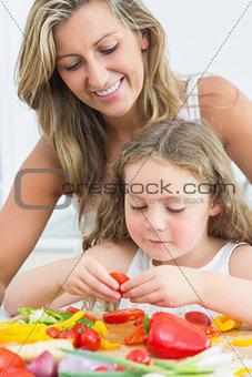 Mother looking at daughter preparing vegetables