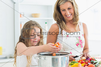 Smiling mother and daughter working at the kitchen