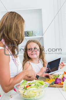Mother cutting vegetables with her daughter using tablet