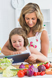 Smiling mother and daughter using tablet