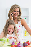 Mother phoning while her daughter working with vegetable