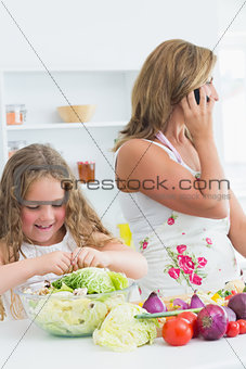Smiling daughter preparing salad while her mother phoning