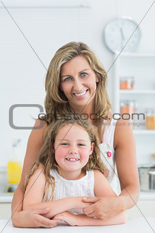 Mother hugging daughter in the kitchen