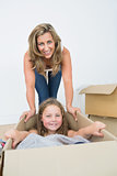 Daughter laying in the box while her mother bows over her