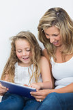 Happy mother and daughter looking at tablet pc