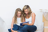 Mother and daughter looking using tablet pc