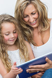 Mother and daughter having fun with tablet computer