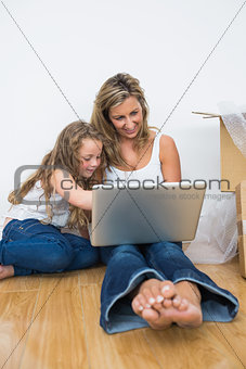 Smiling mother and daughter sitting on the floor