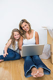 Mother and daughter using laptop sitting on floor