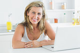 Woman sitting in the kitchen and using laptop