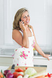 Woman leaning on sink and talking on phone