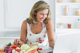 Woman using laptop while preparing vegetables