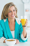 Woman having juice and cereal for breakfast