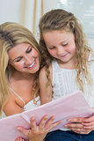 Daughter and mother reading storybook