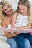 Daughter sitting on mother's lap reading