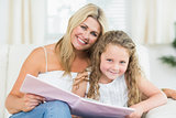 Mother and daughter sitting on the sofa with a book