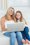 Daughter and mother using notebook