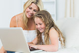 Daughter and mother working with notebook
