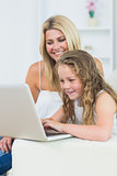 Mother and daughter sitting on the sofa with laptop